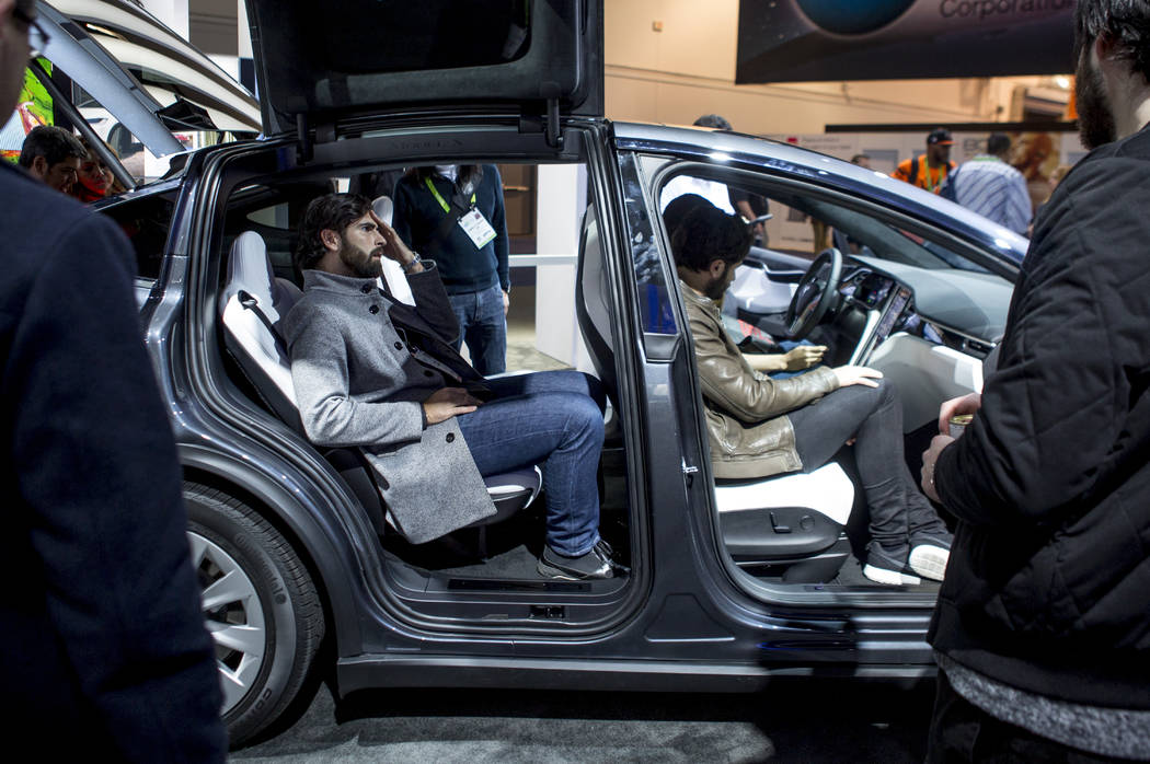 CES attendees sit in a Tesla Model X at CES at the Las Vegas Convention Center on Friday, Jan. 12, 2018. An estimated 180,000 people attended CES this year. Patrick Connolly Las Vegas Review-Journ ...