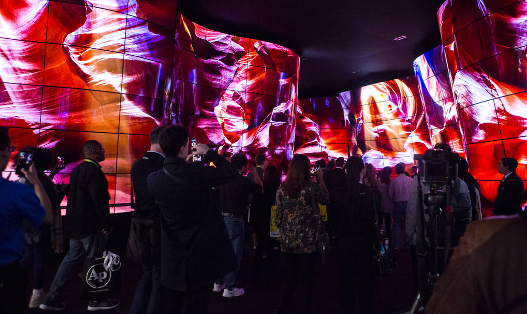 CES attendees walk through a display of OLED TVs from LG at CES at the Las Vegas Convention Center on Friday, Jan. 12, 2018. An estimated 180,000 people attended CES this year. Patrick Connolly La ...