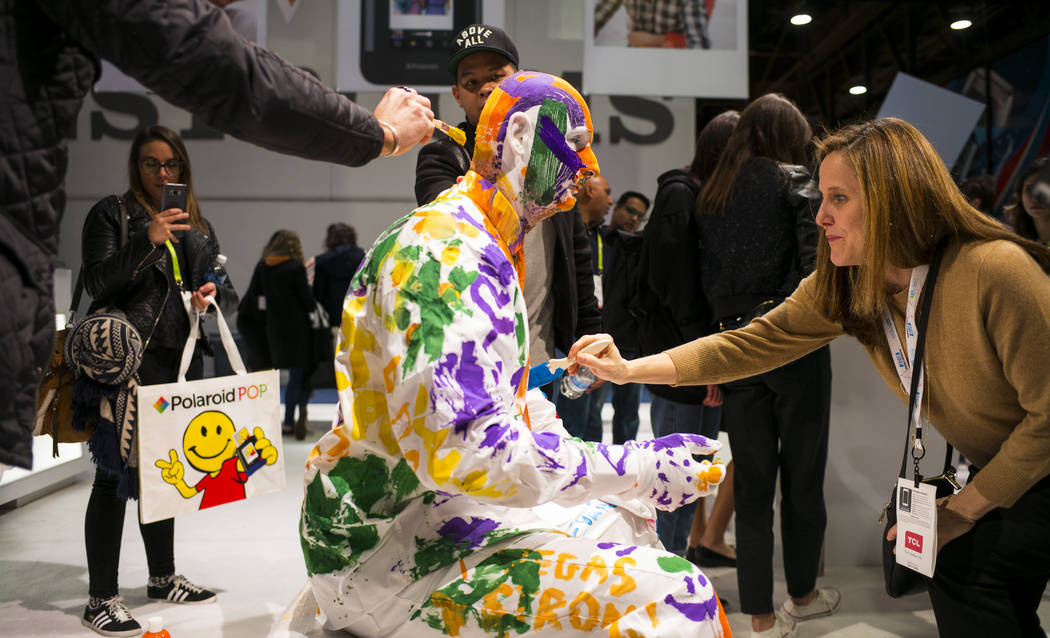 Chani Wiggins, right, joins other attendees in painting John Eicke, a winner of the World Championship of Living Statues, at the Polaroid booth during CES at the Las Vegas Convention Center in Las ...