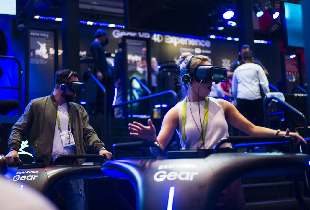 Andrew Tropeano, left, and Michelle Ison, both of NewsWatch, try a virtual reality demonstration from Samsung during CES at the Las Vegas Convention Center in Las Vegas on Friday, Jan. 12, 2018. C ...