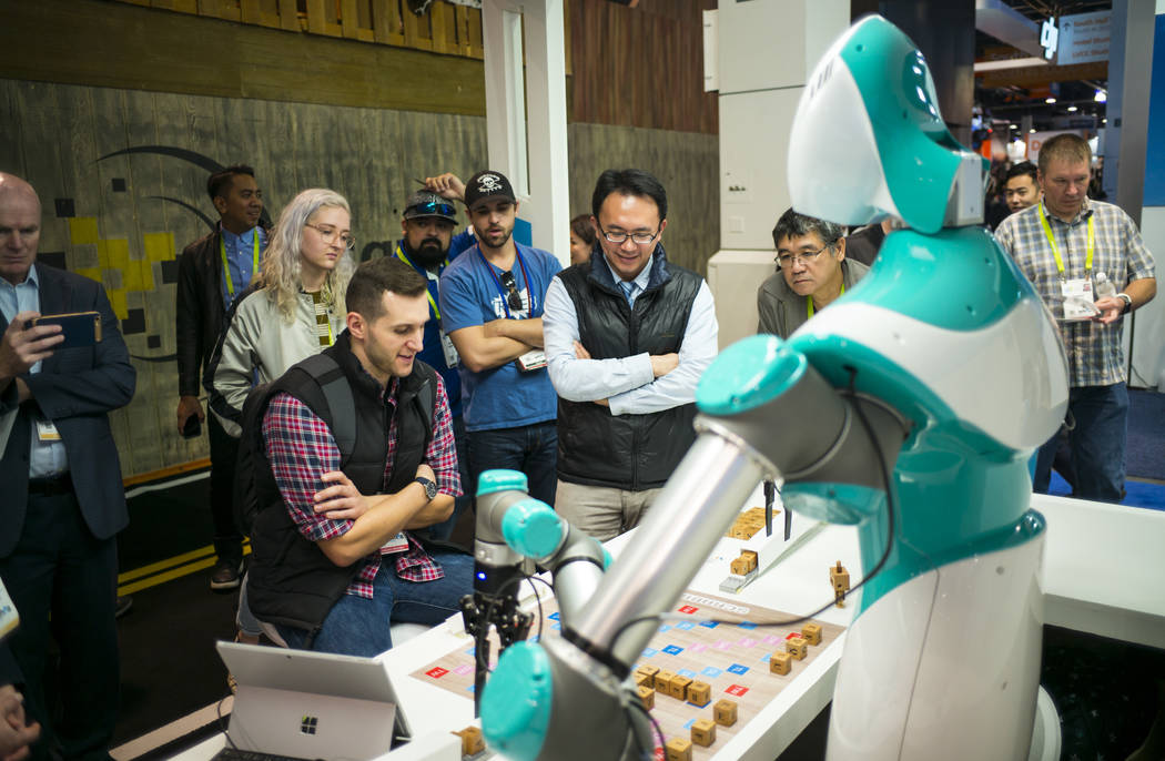 Mark Guarraia of Cambridge, Mass. plays in a game of Scrabble against a robot created by Industrial Technology Research Institute during CES at the Las Vegas Convention Center in Las Vegas on Frid ...