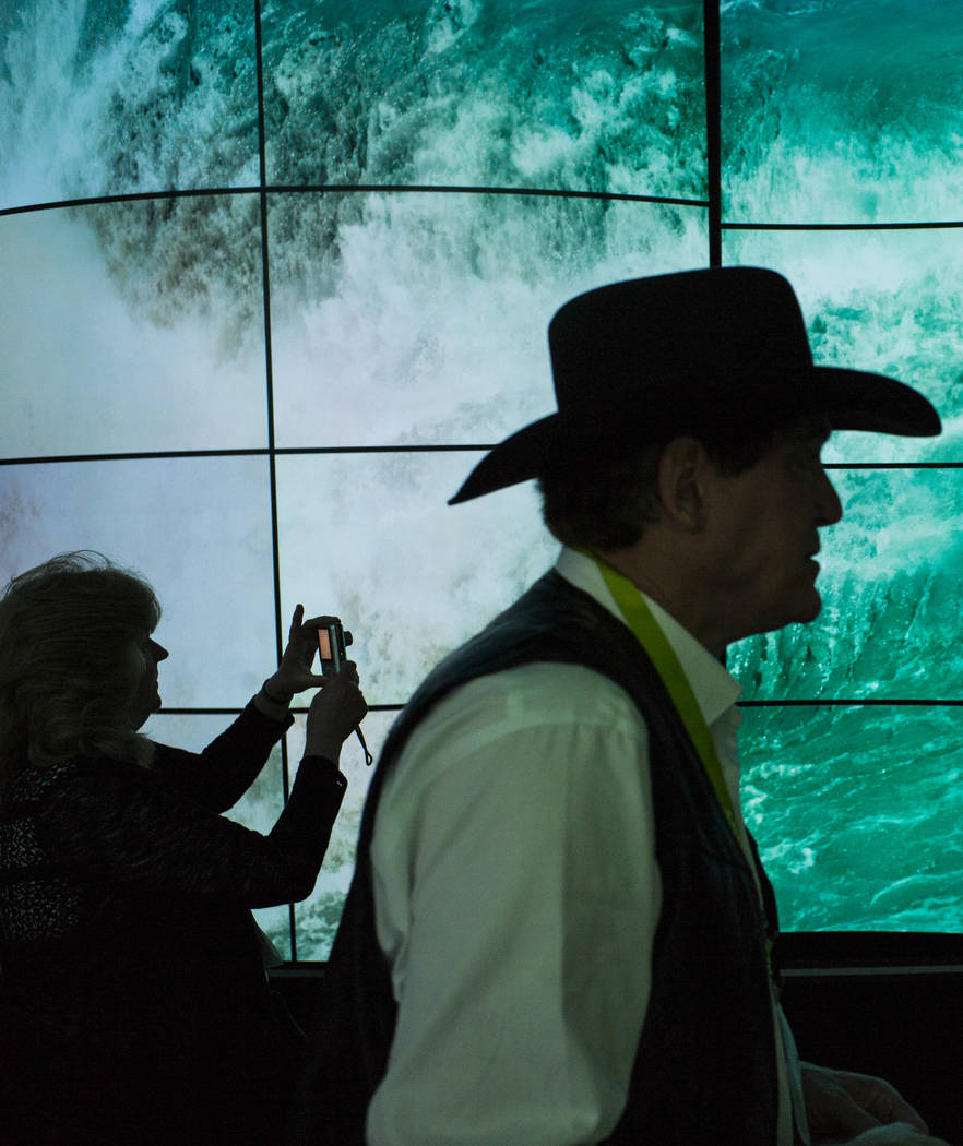 "Attendees are silhouetted as they walk through LG's ""OLED Canyon"" during CES at the Las Vegas Convention Center in Las Vegas on Friday, Jan. 12, 2018. Chase Stevens Las Vegas Rev ..."