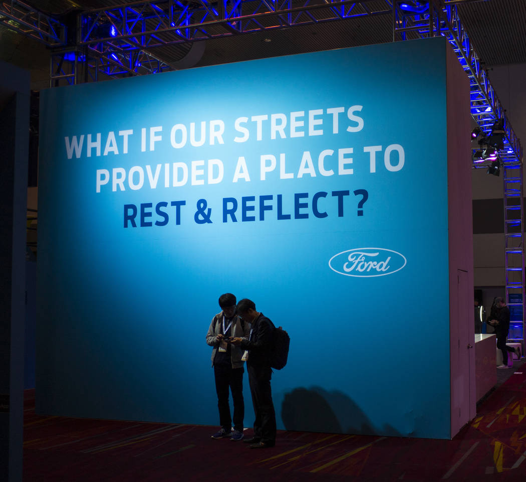 Attendees stand below a Ford advertisement during CES at the Las Vegas Convention Center in Las Vegas on Friday, Jan. 12, 2018. Chase Stevens Las Vegas Review-Journal @csstevensphoto