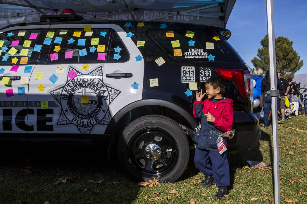 Analu Tam, 6, looks over at his mother after putting an appreciation sticky note on a police car during a Law Enforcement Appreciation Day event at Police Memorial Park on Saturday, Jan. 13, 2018. ...