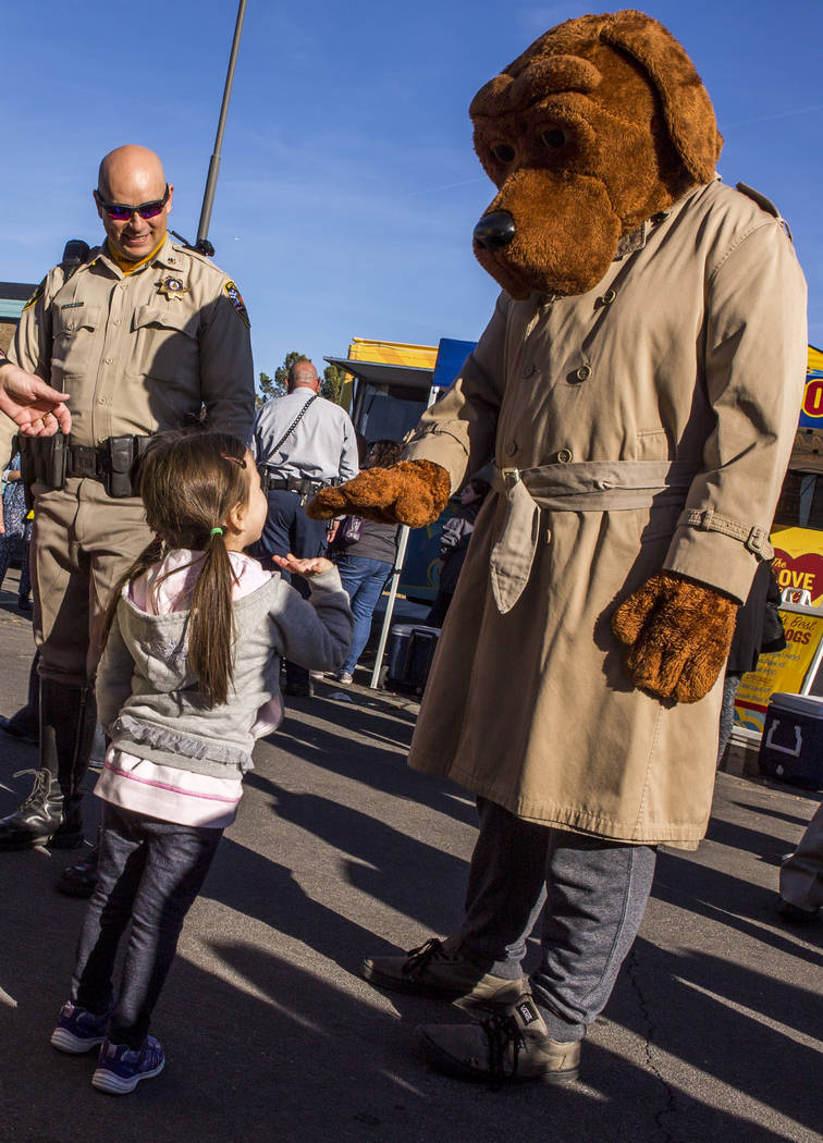 Madison Almaguer, 4, gives McGruff The Crime Dog a high five as her father, Michael Almaguer of LVMPD, stands by during a Law Enforcement Appreciation Day event at Police Memorial Park on Saturday ...
