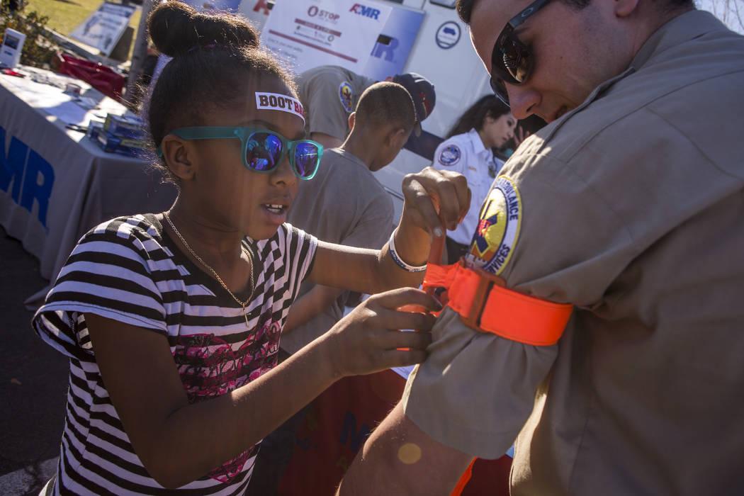 Mariah Williams, 9, practices using a tourniquet on advanced EMT Alex Varela's arm during a Law Enforcement Appreciation Day event at Police Memorial Park on Saturday, Jan. 13, 2018.  Patrick Conn ...