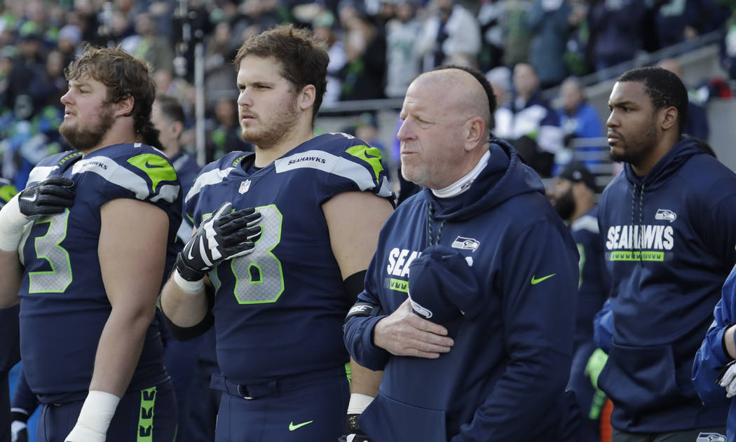 Seattle Seahawks assistant head coach and offensive line coach Tom Cable, second from right, stands with players during the singing of the national anthem before an NFL football game against the A ...