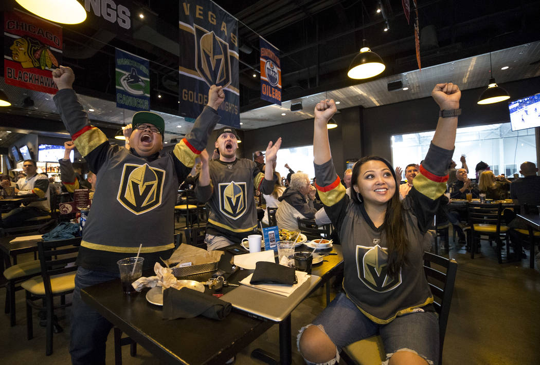 Vegas Golden Knight fans Charles Javier, from left, Jesse Johnston and Charlotte Wolfe celebrate a first-period goal during an away game against the Tampa Bay Lightning at MacKenzie River Pizza, G ...