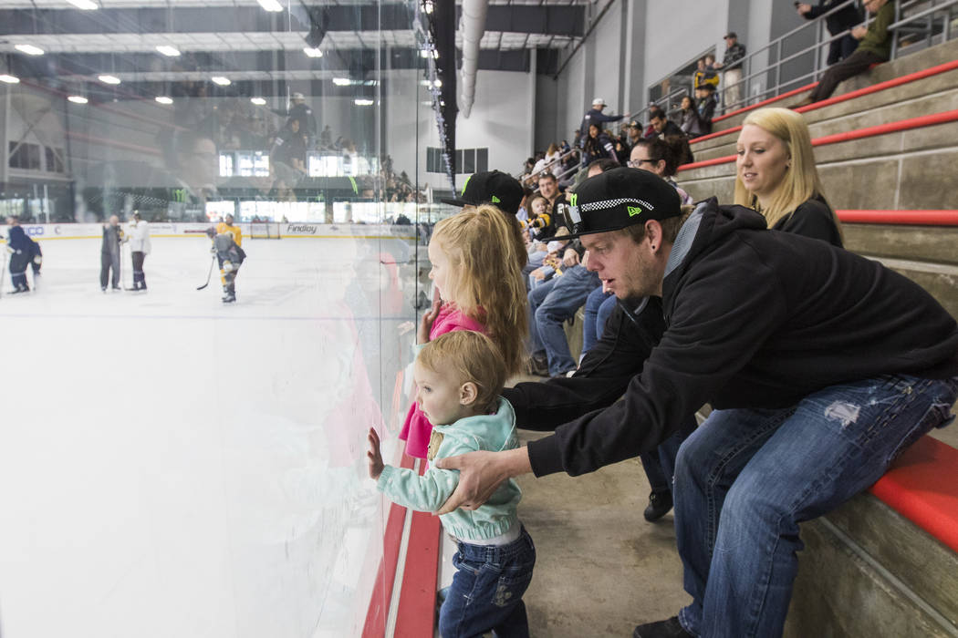 Andrew Alderman holds his daughter Rilyn Adlerman, 19 months, as they watch the Vegas Golden Knights practice alongside his wife Holly Alderman and daughters Adeline Alderman, 3, and Madison Alder ...