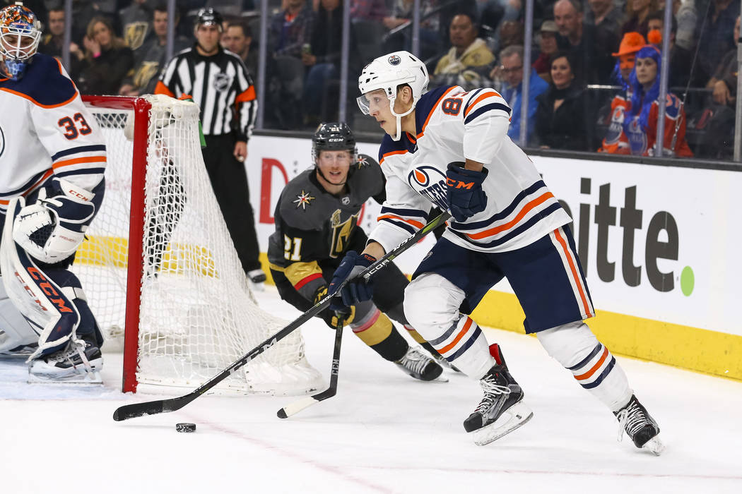 Edmonton Oilers defenseman Matt Benning (83) controls the puck as Vegas Golden Knights center Cody Eakin (21) trails behind during the first period of an NHL hockey game between the Vegas Golden K ...