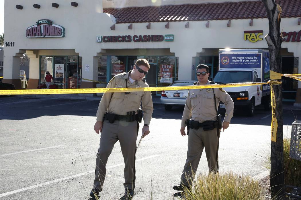 Las Vegas police investigate after a woman was shot in front of a checking cashing store near Jones Boulevard and Vegas Drive on Thursday, Jan. 11, 2018, in Las Vegas. She died at University Medic ...