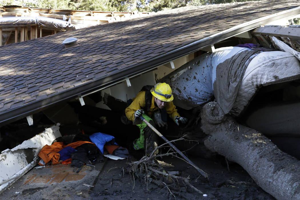 Colette Layton, bottom, of the Atascadero Fire Dept, searches a home Saturday, Jan. 13, 2018, in Montecito, Calif. (AP Photo/Marcio Jose Sanchez)