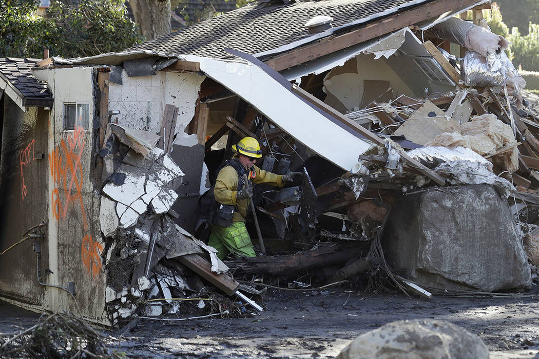 A firefighter searches a destroyed home Saturday, Jan. 13, 2018, in Montecito, Calif. (AP Photo/Marcio Jose Sanchez)