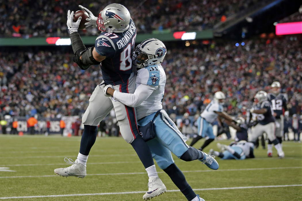 New England Patriots tight end Rob Gronkowski catches a touchdown pass with Tennessee Titans safety Kevin Byard (31) defending during the second half of an NFL divisional playoff football game, Sa ...