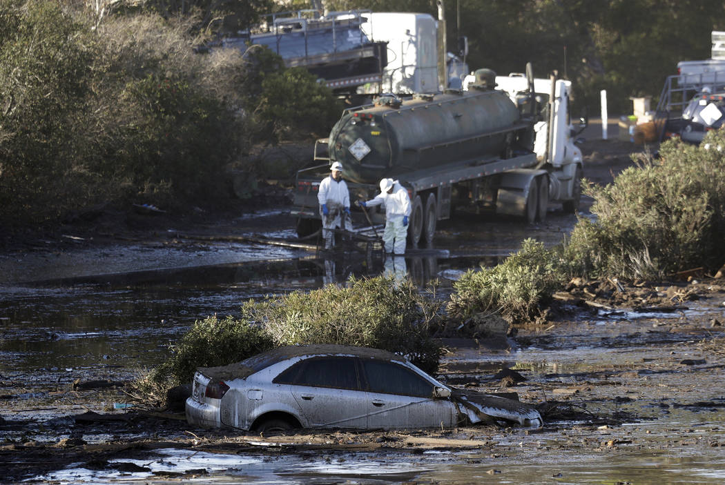 Crews pump mud on Highway 101 after a mudslide Saturday, Jan. 13, 2018, in Montecito, Calif.  Most of the people of Montecito, a town usually known for its serenity and luxury, were under orders t ...