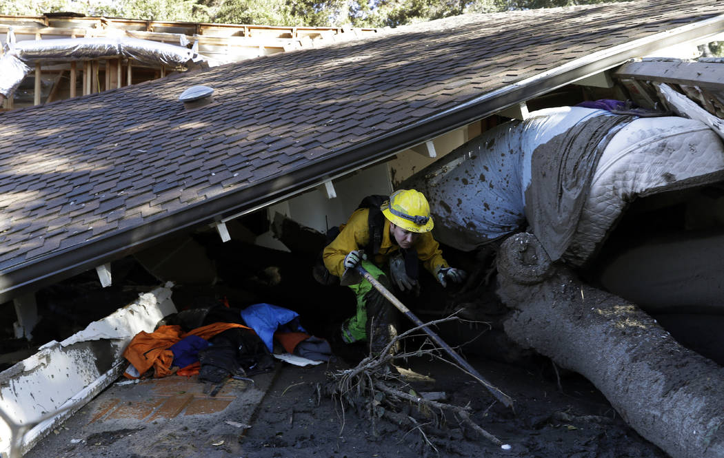 Colette Layton, bottom, of the Atascadero Fire Dept, searches a home Saturday, Jan. 13, 2018, in Montecito, Calif.  Most of the people of Montecito, a town usually known for its serenity and luxur ...
