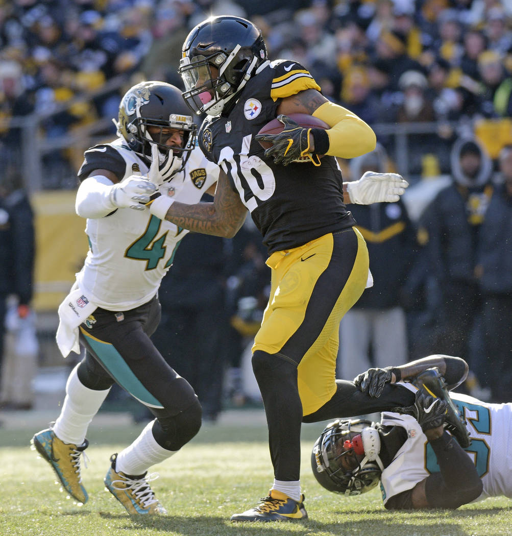 Pittsburgh Steelers running back Le'Veon Bell (26) is tackled by Jacksonville Jaguars free safety Tashaun Gipson, lower right, and strong safety Barry Church, left, during the first half of an NFL ...