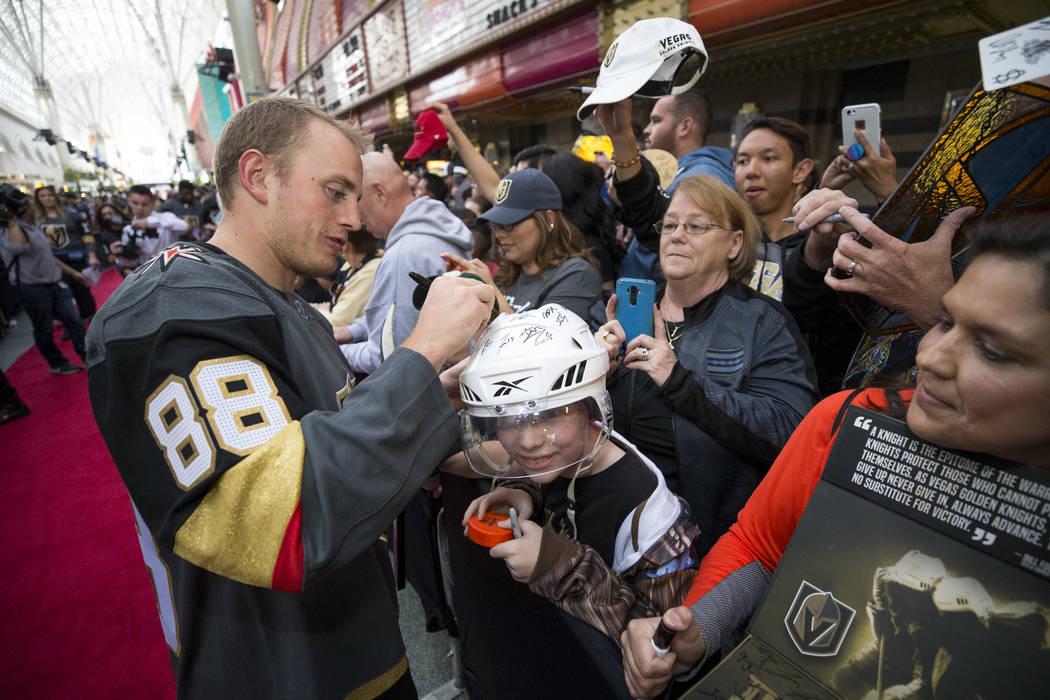 Vegas Golden Knights defenseman Nate Schmidt (88) autographs the helmet of Las Vegas resident Hunter Klingenneier, 12, during the team's first fan fest at the Fremont Street Experience in downtown ...