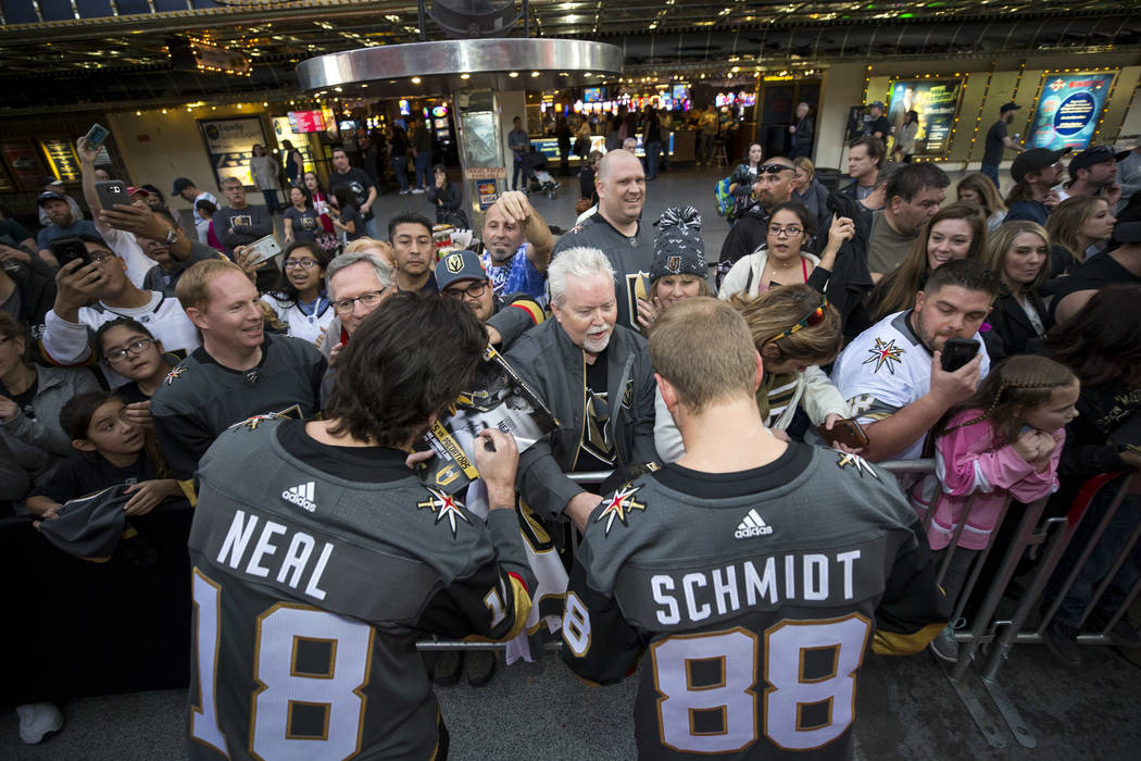 Vegas Golden Knights left wing James Neal (18) and defenseman Nate Schmidt (88) sign autographs during the team's first fan fest at the Fremont Street Experience in downtown Las Vegas on Sunday, J ...