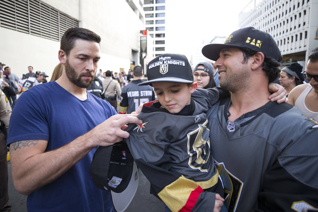 Vegas Golden Knights defenseman Deryk Engelland, left, signs the jersey of Tristen Sterbens, 6, as his stepfather, Mike Foskaris, hold him up during the team's first fan fest at the Fremont Street ...