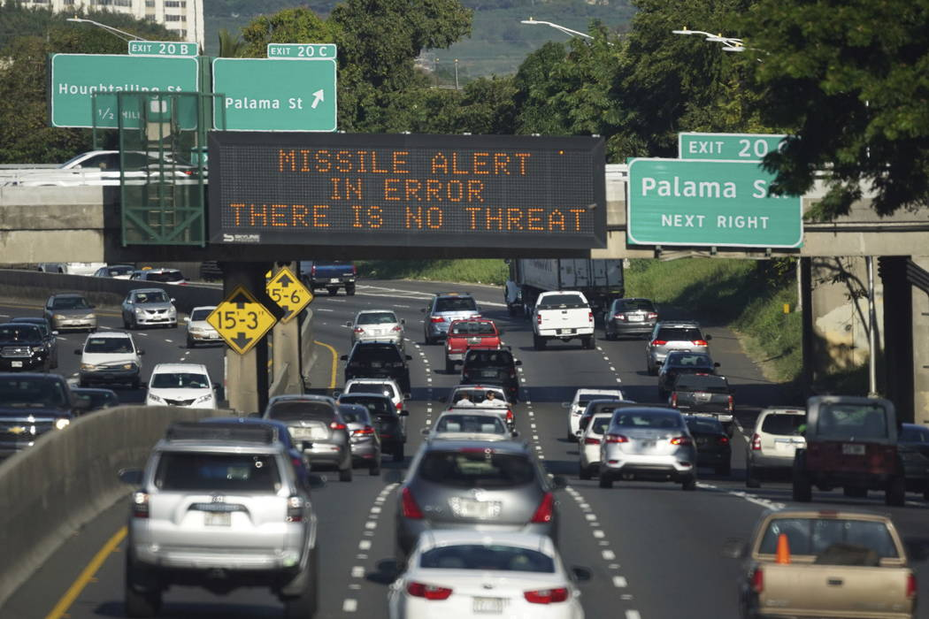 "Cars drive past a highway sign that says ""MISSILE ALERT ERROR THERE IS NO THREAT"" on the H-1 Freeway in Honolulu.  (Anthony Quintano/Civil Beat via AP)"