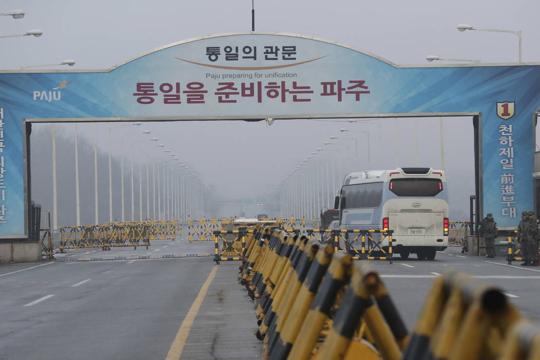 A bus carrying the South Korean delegations passes as South Korean soldier salutes at Unification Bridge, which leads to the Panmunjom in the Demilitarized Zone in Paju, South Korea, Monday, Jan.  ...