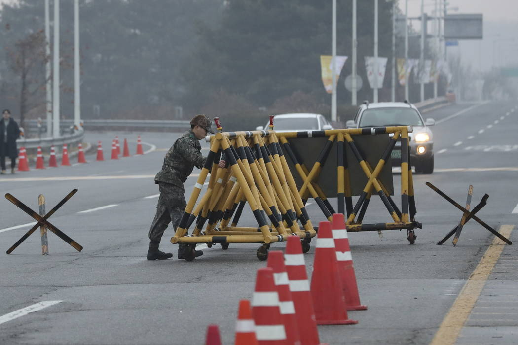 A South Korean soldier adjusts barricade before South Korea's delegation vehicle's arriving at Unification Bridge, which leads to the Panmunjom in the Demilitarized Zone in Paju, South Korea, Mond ...