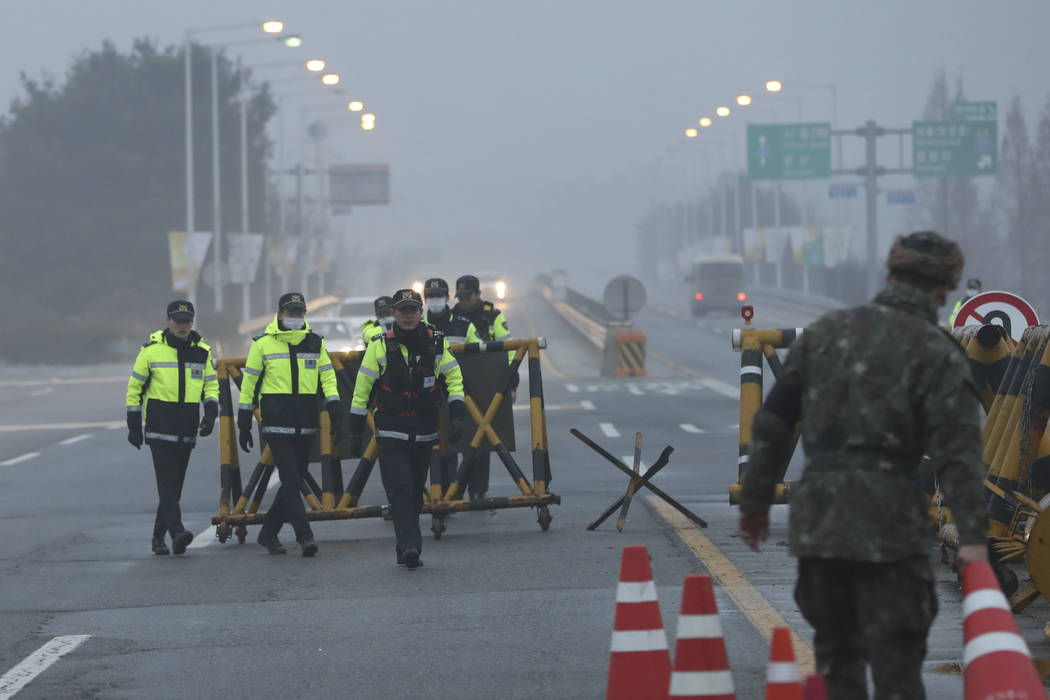 South Korean police officers and soldier walk near barricades before South Korea's delegation vehicle's arriving at Unification Bridge, which leads to the Panmunjom in the Demilitarized Zone in Pa ...