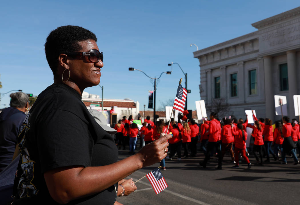 "Angela Henderson watches the 36th annual Dr. Martin Luther King Jr. Parade, themed ""Living the Dream: Building a Bridge to Unity,"" in downtown Las Vegas, Jan. 15, 2018. The parade featured floats, ..."