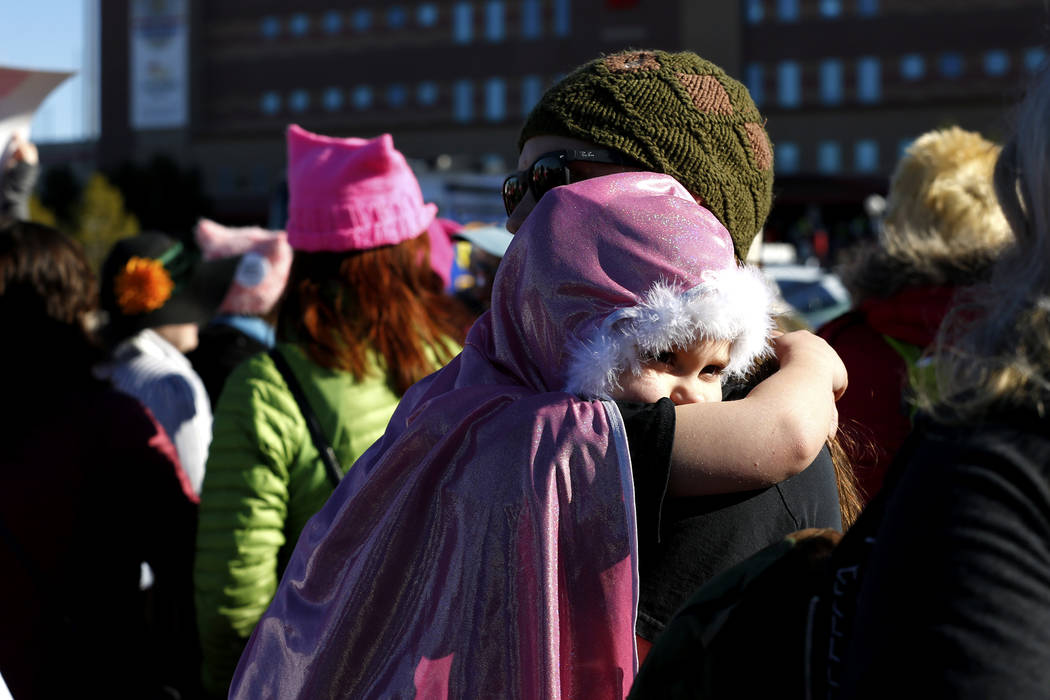 Kyle Fuhrman, 32, of Arizona, carries his daughter Wren, 6, during the Power to the Polls event, hosted by the Women's March, at the Sam Boyd Stadium in Las Vegas, Jan. 21, 2018. The event, which  ...