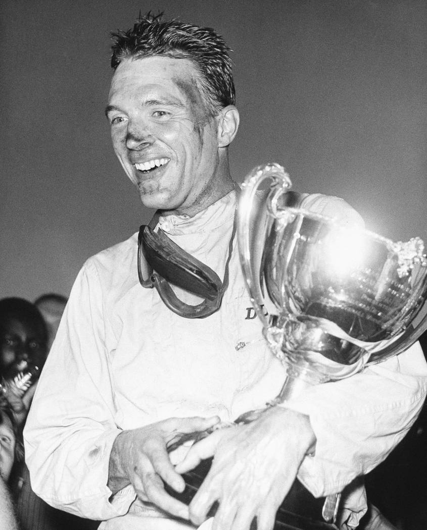 FILE - This Dec. 9, 1962 file photo shows Dan Gurney holding a trophy in Nassau, Bahamas. Gurney, the first driver to win in Formula One, IndyCar and NASCAR, died Sunday, Jan. 14, 2018 from compli ...