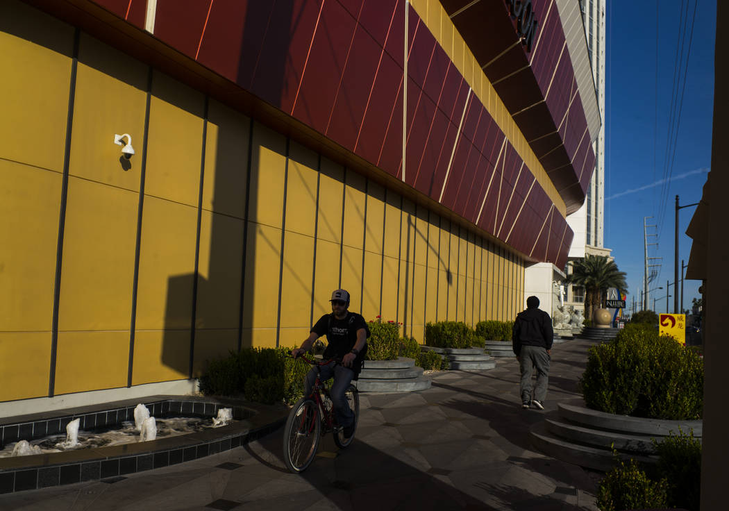 A pedestrian and cyclist pass by the exterior of Lucky Dragon, which shut down gaming and casino restaurant operations in early Jan., in Las Vegas on Monday, Jan. 15, 2018. (Chase Stevens/Las Vega ...