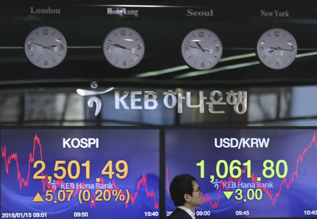 A currency trader walks by the screens showing the Korea Composite Stock Price Index (KOSPI), left, and the foreign exchange rate between U.S. dollar and South Korean won at the foreign exchange d ...