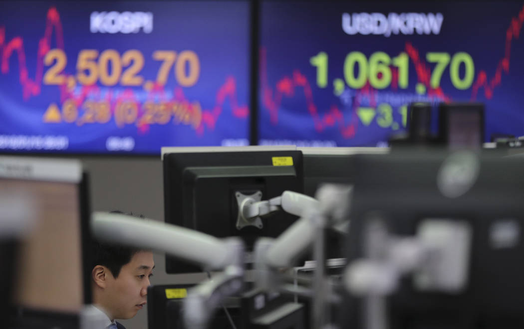 A currency trader watches the computer monitors near the screens showing the Korea Composite Stock Price Index (KOSPI), left, and the foreign exchange rate between U.S. dollar and South Korean won ...