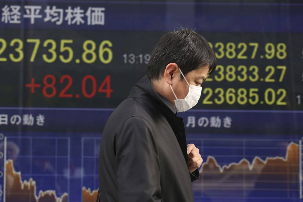A man walks by an electronic stock board of a securities firm in Tokyo, Monday, Jan. 15, 2018. Asian stock markets edged higher on Monday after Wall Street's strong finish last week. The U.S. doll ...