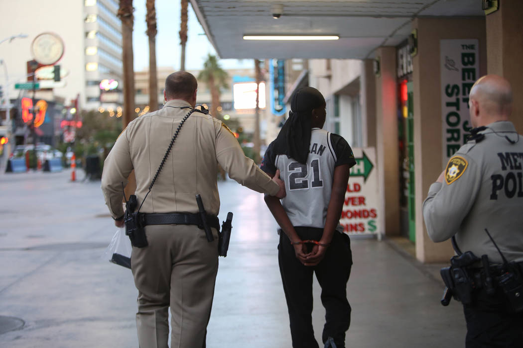 A Metro officer walks away an arrested individual near the Fremont Street Experience in Las Vegas, Monday, Jan. 15, 2018. A large fight occurred nearby with around 100 people involved and eight we ...