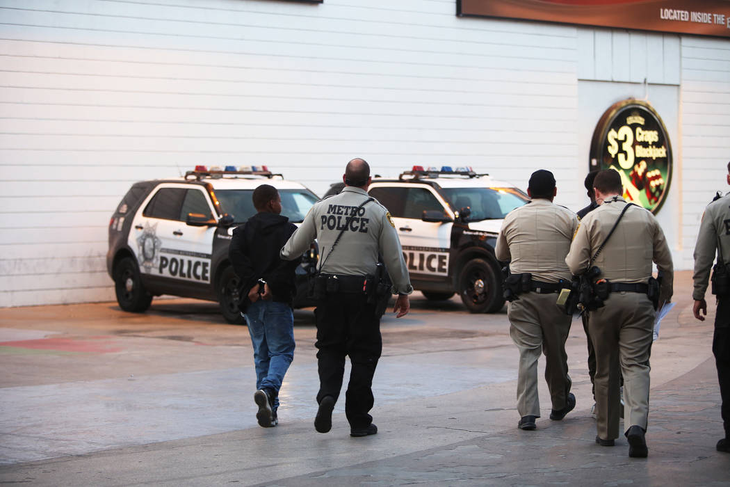 Metro officers walk away with handcuffed individuals near the Fremont Street Experience in Las Vegas, Monday, Jan. 15, 2018. A large fight occurred nearby with around 100 people involved and eight ...