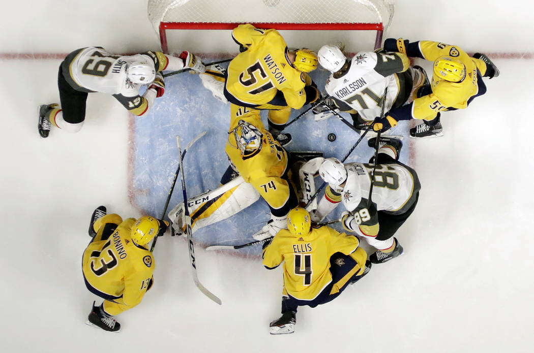 Nashville Predators goalie Juuse Saros (74), of Finland, blocks a shot against the Vegas Golden Knights as a swarm of players fight for the rebound in the second period of an NHL hockey game Tuesd ...