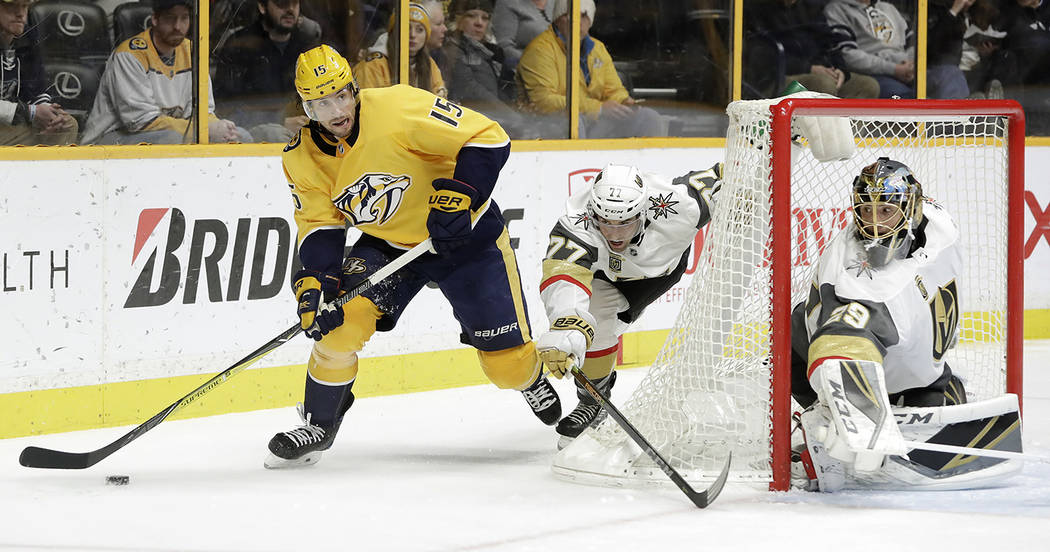 Nashville Predators right wing Craig Smith (15) closes in on the net as Vegas Golden Knights' Brad Hunt (77) and goalie Marc-Andre Fleury (29) defend in the second period of an NHL hockey game Tue ...
