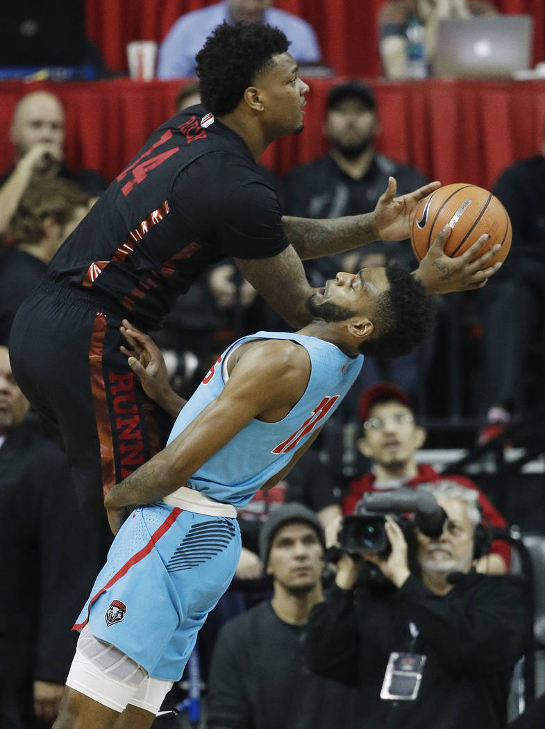 UNLV's Tervell Beck, left, fouls New Mexico's Jachai Simmons during the first half of an NCAA college basketball game Wednesday, Jan. 17, 2018, in Las Vegas. (AP Photo/John Locher)