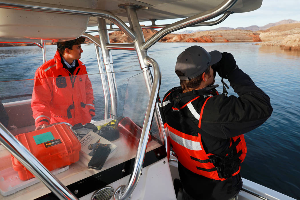 Southern Region Supervising Biologist Joe Barnes, 39, right, and environmental protections specialist Ben Smith, 30, scan the sky for bald eagles at Lake Mead National Recreation Area, Wednesday,  ...
