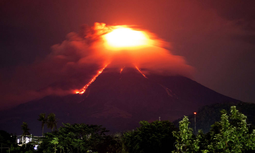 Lava cascades down the slopes of Mayon volcano as seen from Legazpi city, Albay province, around 340 kilometers (210 miles) southeast of Manila, Philippines, Monday, Jan. 15, 2018. More than 9,000 ...