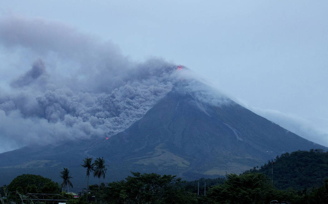 Lava continues to cascade down the slopes of Mayon volcano as seen from Legazpi city, Albay province, around 340 kilometers (210 miles) southeast of Manila, Philippines, Tuesday, Jan. 16, 2018. Gl ...