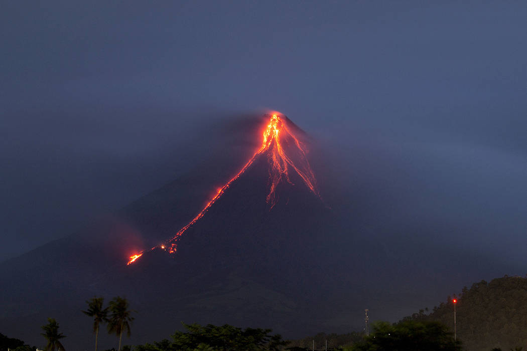 Lava continues to cascade down the slopes of Mayon volcano as seen from Legazpi city, Albay province, around 340 kilometers (210 miles) southeast of Manila, Philippines, at dawn Tuesday, Jan. 16,  ...