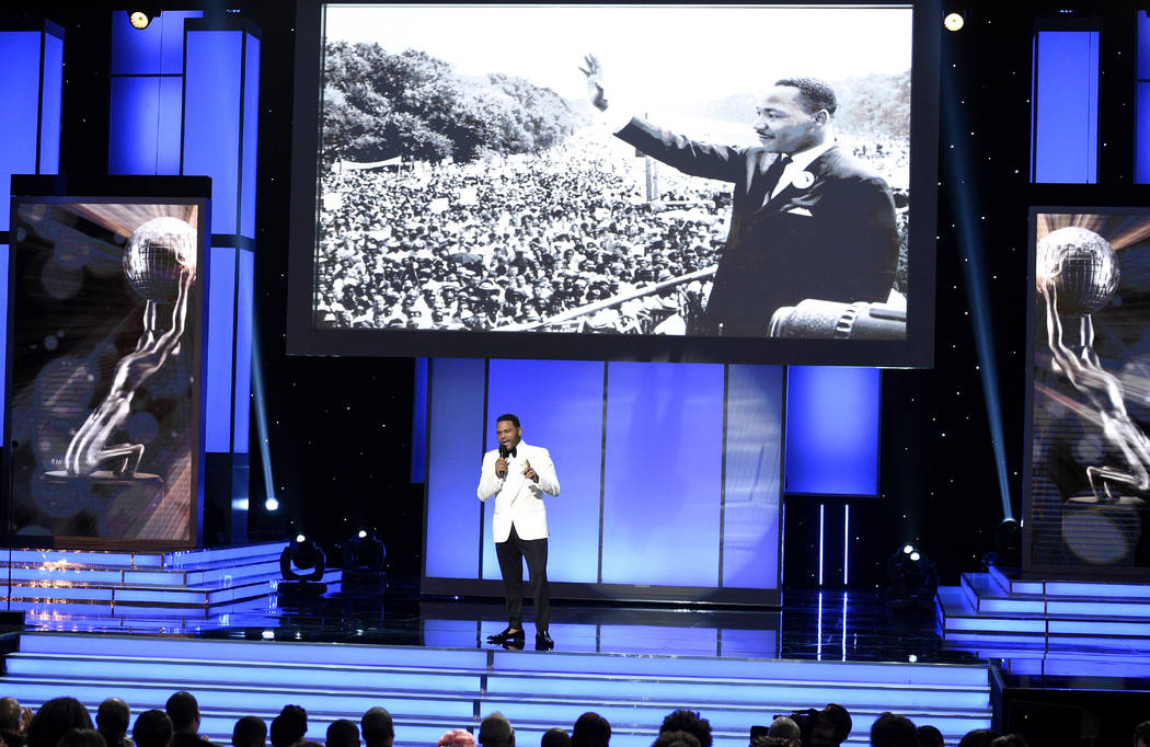 Host Anthony Anderson speaks as Martin Luther King Jr. appears onscreen at the 49th annual NAACP Image Awards at the Pasadena Civic Auditorium on Monday, Jan. 15, 2018, in Pasadena, Calif. (Photo  ...