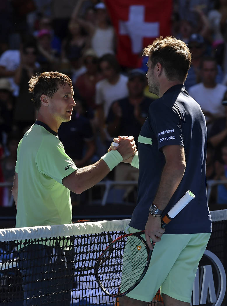 Switzerland's Stan Wawrinka, right, is celebrated by Lithuania's Ricardas Berankis as he won their first round match at the Australian Open tennis championships in Melbourne, Australia, Tuesday, J ...