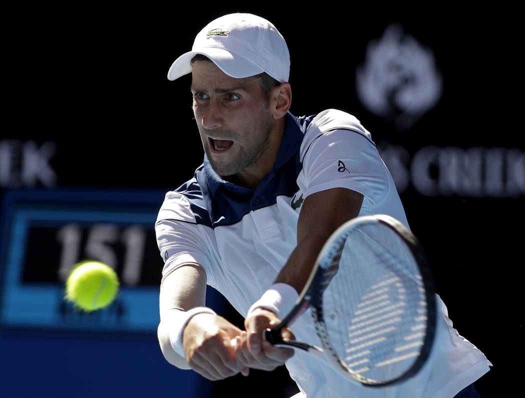 Serbia's Novak Djokovic makes a backhand return to United States' Donald Young during their first round match at the Australian Open tennis championships in Melbourne, Australia, Tuesday, Jan. 16, ...