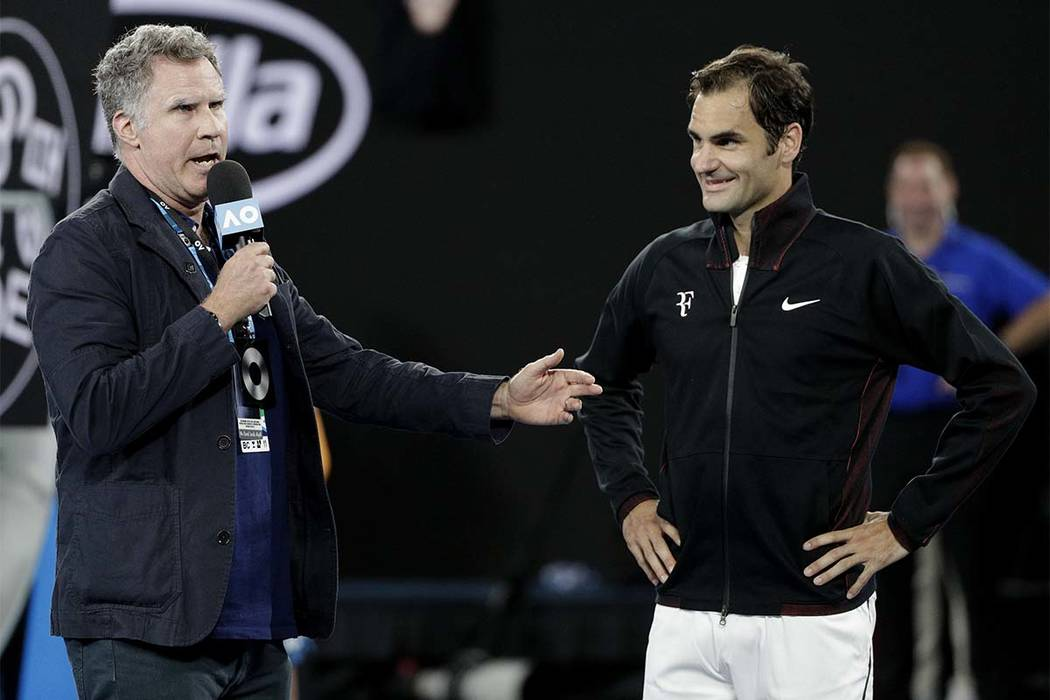 U.S. actor Will Ferrell, left, interviews Switzerland's Roger Federer on Rod Laver Arena following his first-round match against Slovenia's Aljaz Bedene at the Australian Open in Melbourne, Austra ...