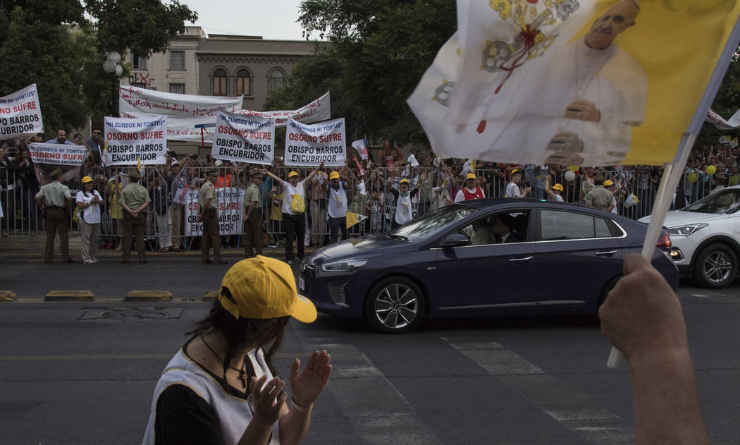 Demonstrators protest against the Catholic church and the visit of Pope Francis as Pope Francis drives by, in Santiago, Chile, Monday, Jan. 15, 2018. Francis' visit to Chile is expected to be frau ...