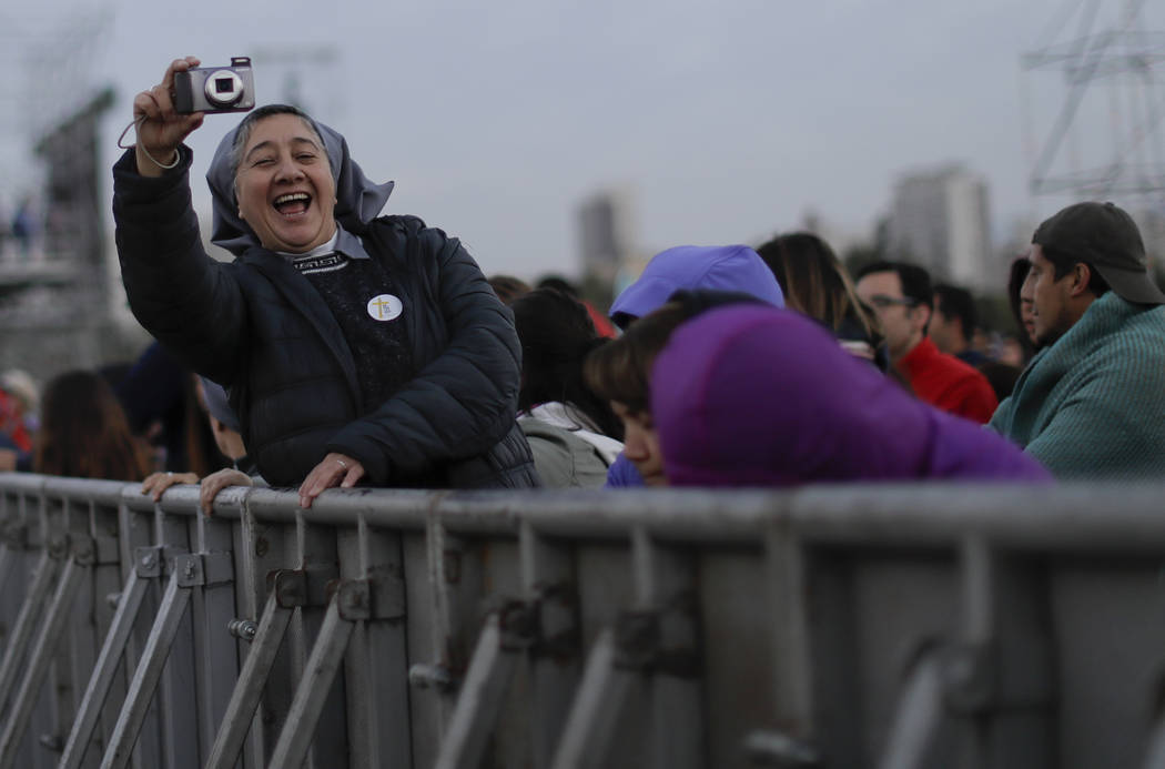 A nun takes a picture as she waits for Pope Francis to celebrate Mass at O'Higgins Park in Santiago, Chile, Tuesday, Jan. 16, 2018. (Natacha Pisarenko/AP)